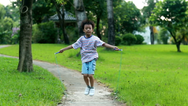 little boy jumping rope on grass - skipping stock videos & royalty-free footage