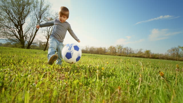 slo mo little boy kicking a ball in in the meadow in sunshine - drive ball sports stock videos & royalty-free footage