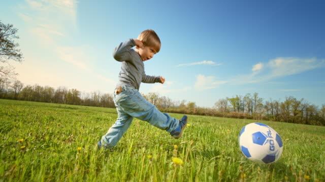slo mo ts kleiner junge kickt einen fußball auf der sonnigen wiese - langsam stock-videos und b-roll-filmmaterial