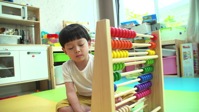 4K: Little boy learning by counting with abacus at his home.