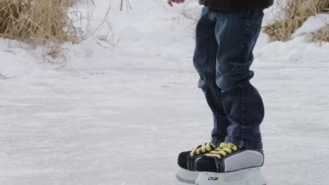 little boy learning to ice skate on a pond outside - pond stock videos & royalty-free footage