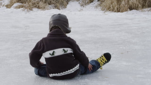 little boy learning to ice skate on a pond outside - falling stock videos and b-roll footage