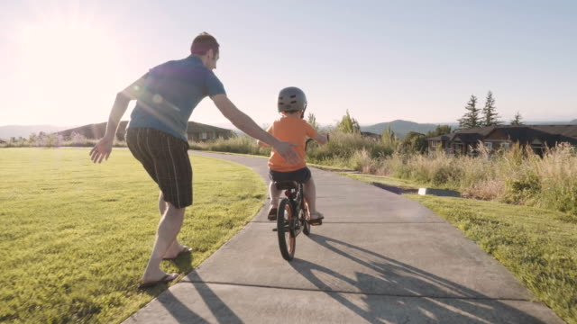 little boy learning to ride his bike - attività del fine settimana video stock e b–roll