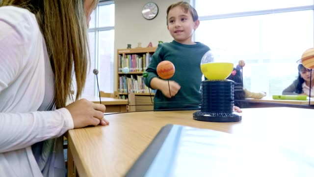 kleiner junge erfährt während des naturwissenschaftsunterrichts etwas über das sonnensystem - astronomie stock-videos und b-roll-filmmaterial