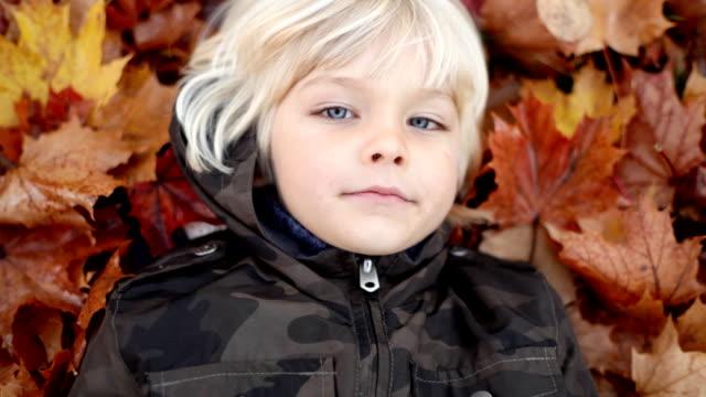 Kleine Junge liegen im Herbst Blätter