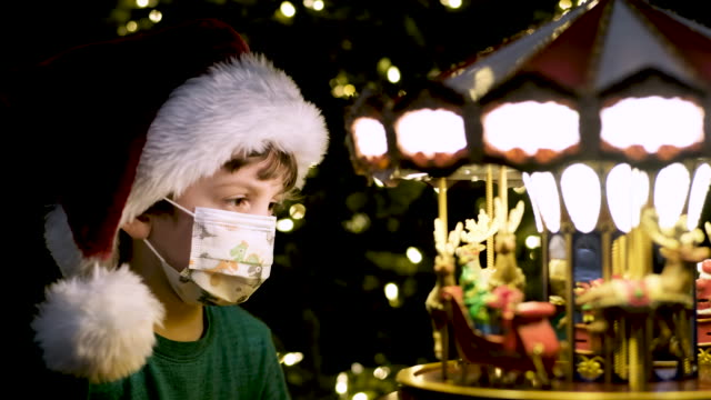 little boy looking at a toy carrousel wearing a santa hat and a protective face mask - loneliness stock videos & royalty-free footage
