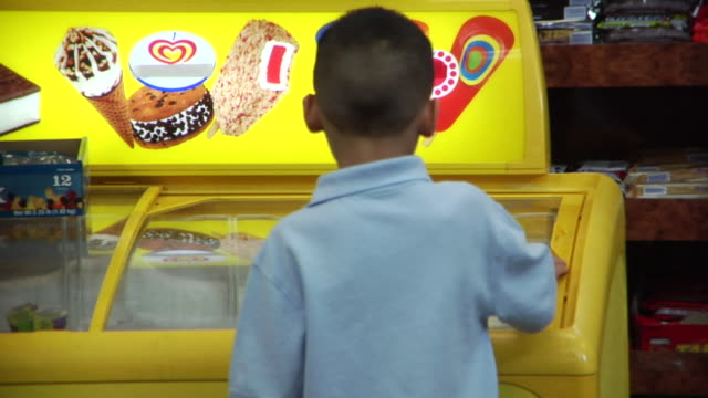CU little boy looking at ice cream freezer in convenience store/ Brooklyn, New York