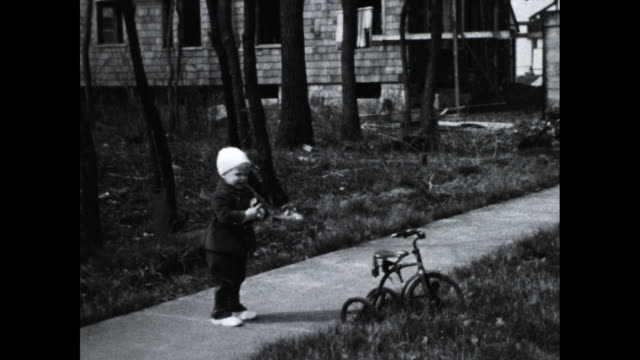 vídeos de stock e filmes b-roll de little boy looking at the camera moving a tricycle from the sidewalk to the lawn - moving activity