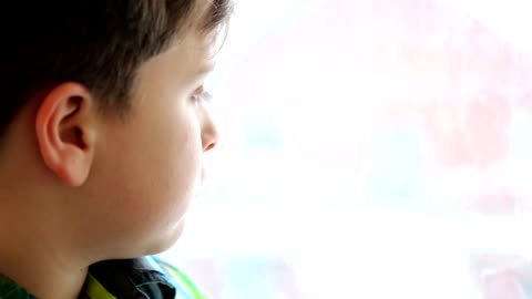 little boy looking out of the window on winter - cold temperature stock videos & royalty-free footage