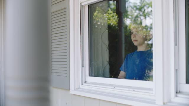 stockvideo's en b-roll-footage met slo mo. little boy looking outside from his home window. - klem