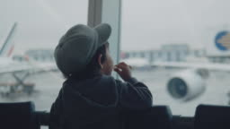 A little boy looks at the planes at the airport.