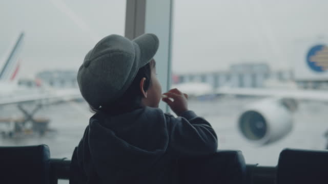 a little boy looks at the planes at the airport. - baby boys stock videos & royalty-free footage