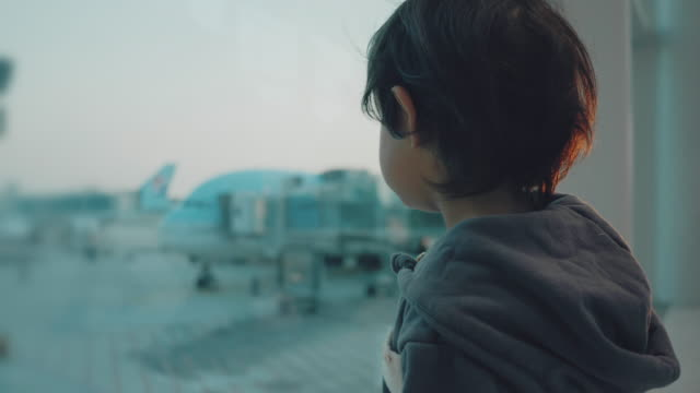 vídeos de stock e filmes b-roll de a little boy looks at the planes at the airport. - bebés meninos