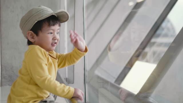 小さな男の子は、空港で飛行機に見えます。 - 立ち去る点の映像素材/bロール