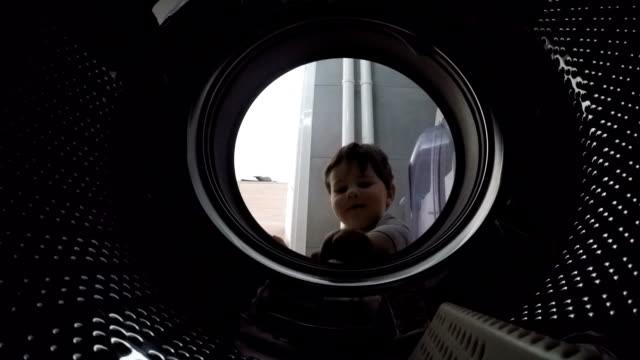 little boy looks into the empty drum washing machine - laundry stock videos and b-roll footage