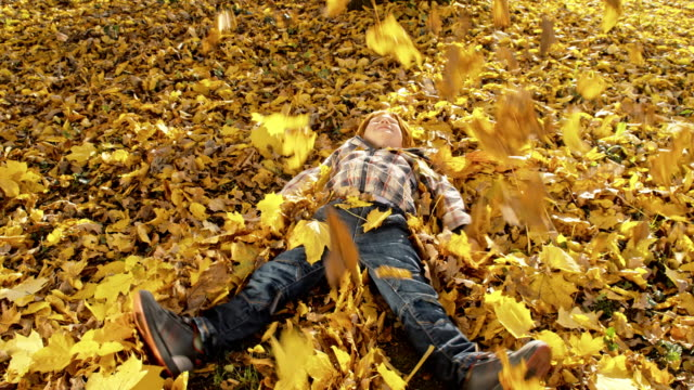 little boy making angel in autumn leaves - lying on back stock videos and b-roll footage