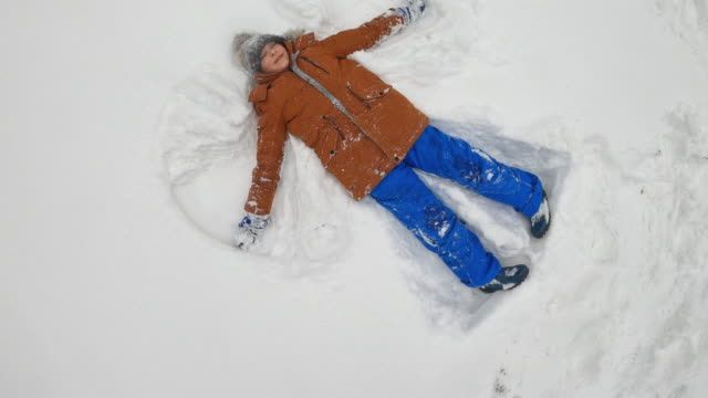 little boy making snow angels in deep snow - imgorthand stock videos & royalty-free footage