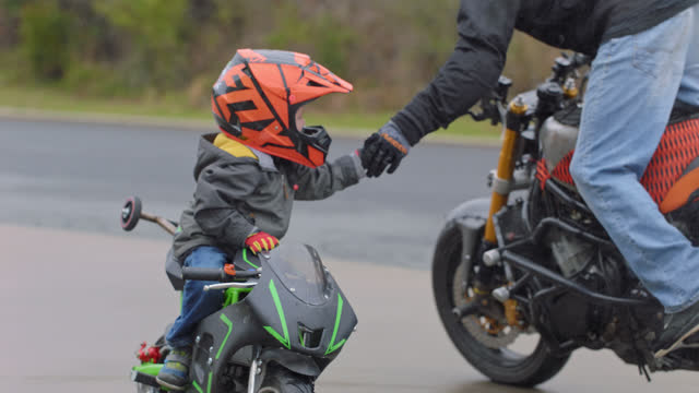stockvideo's en b-roll-footage met slo mo. little boy on a child size stunt bike holds out his hand to a professional stunt motorcycle rider making a circle around him - sporthelm