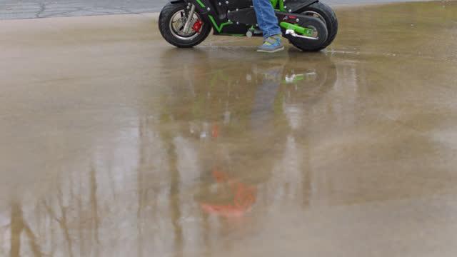vídeos de stock e filmes b-roll de slo mo. little boy on a child size stunt bike rides in circles on the wet pavement of an empty parking lot - perigo