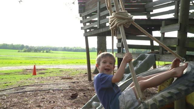 little boy on a farm tire swing super slow motion. - tire swing stock videos & royalty-free footage