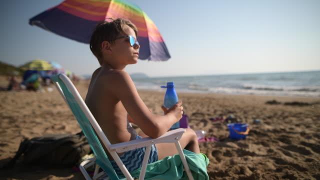 little boy on beach drinking from reusable water bottle. - bottle stock videos & royalty-free footage