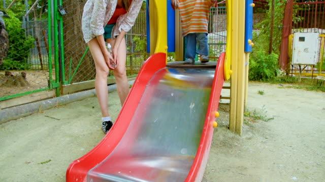 vídeos de stock e filmes b-roll de little boy on children slide - baloiço