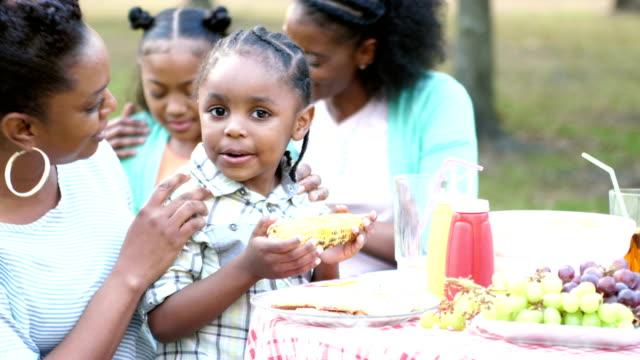 Kleiner Junge auf Mutters Schoß bei Familie Cookout essen Mais