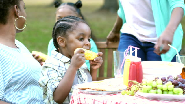 Little boy on  mother's lap at family cookout eating corn