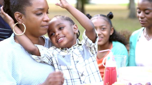 Kleiner Junge auf Mutters Schoß trinken bei Grillparty