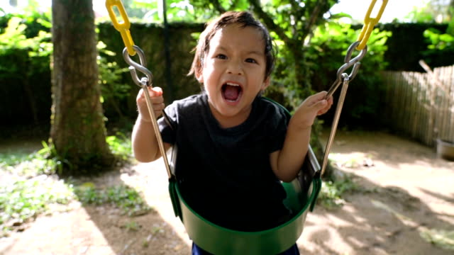 slo mo little boy on swing. - swinging stock videos & royalty-free footage
