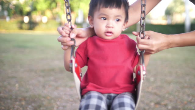 slo mo little boy on swing - sporting term stock videos and b-roll footage