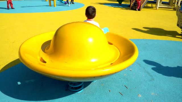 4 k 遊び場 - 在庫ビデオ カルーセルの小さな男の子 - 自閉症点の映像素材/bロール