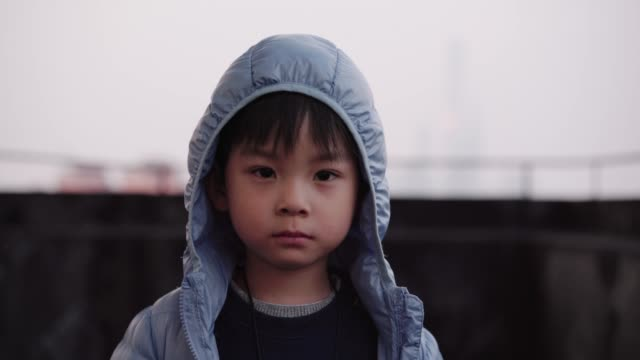 a little boy on the rooftop of tall building in shanghai china - luftverschmutzung stock-videos und b-roll-filmmaterial