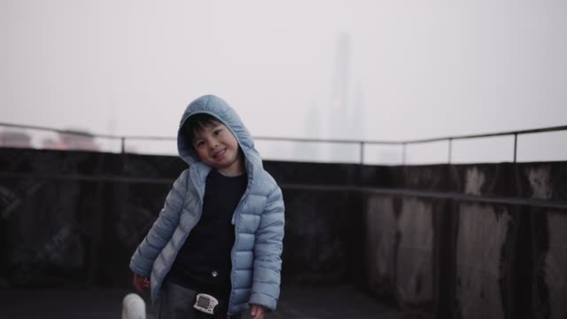 A little boy on the rooftop of tall building in Shanghai China