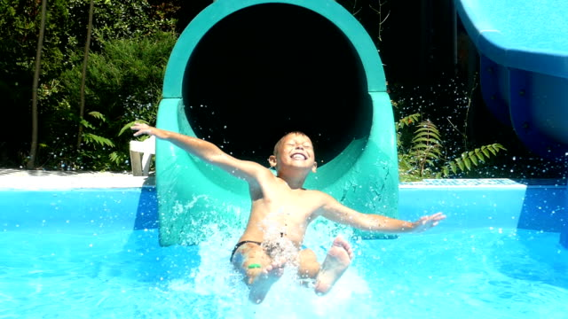 Little boy on the water slides in the water park (slow motion)