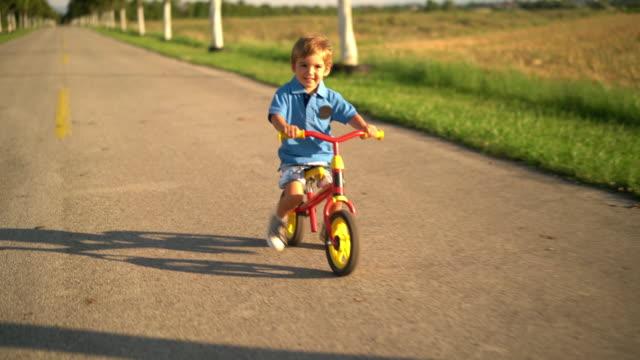 little boy on walking bike - korta ärmar bildbanksvideor och videomaterial från bakom kulisserna