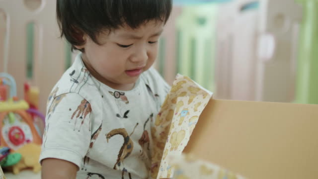 a little boy opening gift box. - unwrapping stock videos & royalty-free footage