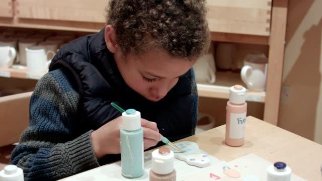HD: Little Boy Painting Clay Figure