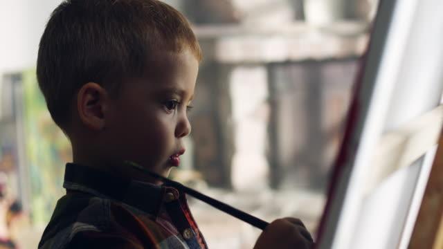 stockvideo's en b-roll-footage met jongetje schilderen - om teken