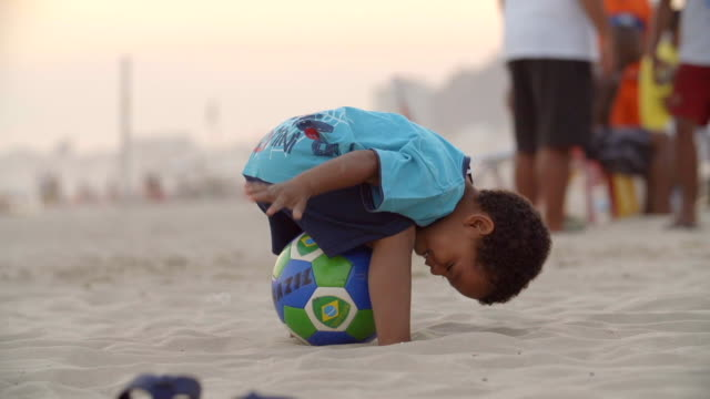 little boy pats and poses with brazilian soccer ball on copacabana beach - international soccer event stock videos & royalty-free footage