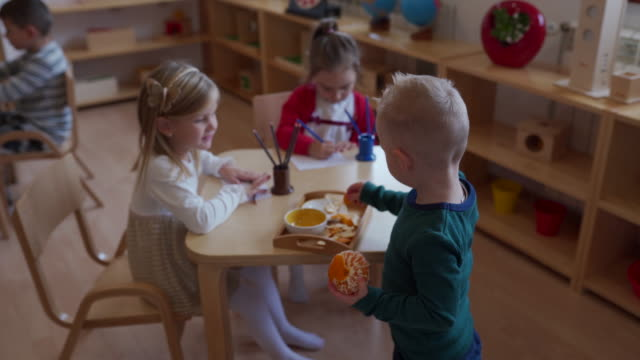 little boy peeling an orange in preschool classroom - school meal stock videos & royalty-free footage