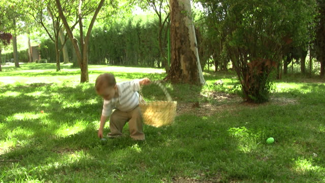 Little boy picking up easter eggs