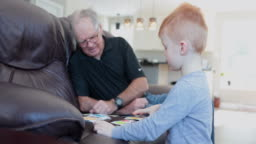 Little Boy playing cards games with his Grandfather while in quarantine at home