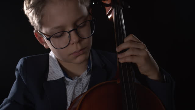 vidéos et rushes de petit garçon jouant le violoncelle sur l'étape - violoncelle