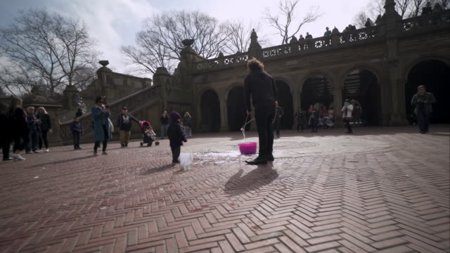 little boy playing in bubbles on central park's bethesda terrace in new york city - street performer stock videos & royalty-free footage