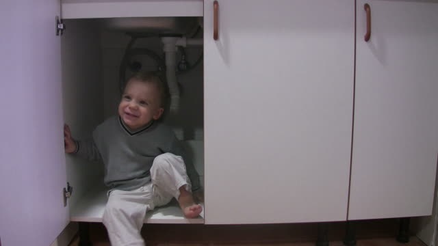 little boy playing in kitchen cabinet - cupboard stock videos & royalty-free footage