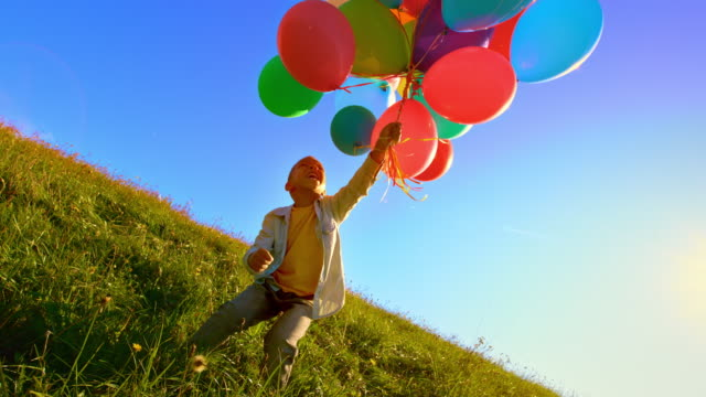 vídeos y material grabado en eventos de stock de slo mo niño jugando en el prado con un montón de globos de colores - globo de helio