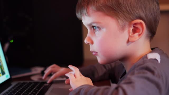 vídeos y material grabado en eventos de stock de niño pequeño jugando en una computadora portátil en casa - malos hábitos