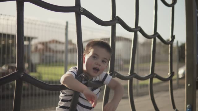 Little boy playing on a rope ladder