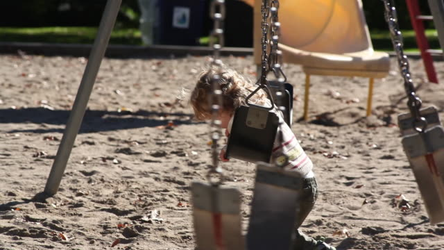 ms little boy playing  on swing in park / toronto, ontario, canada - kelly mason videos stock-videos und b-roll-filmmaterial